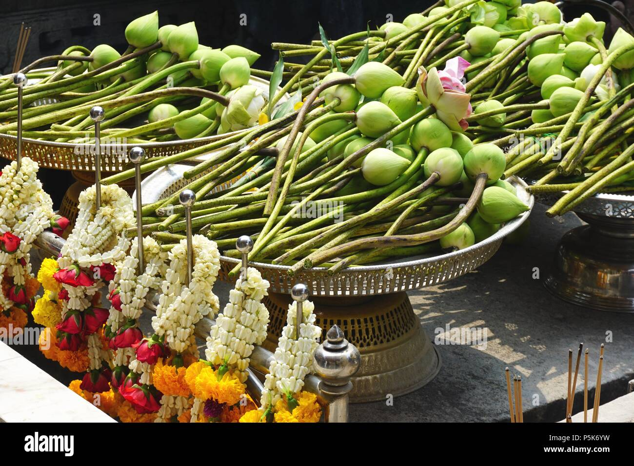 Lotus Flower Blossoms And Colorful Floral Garlands Piled On An Altar