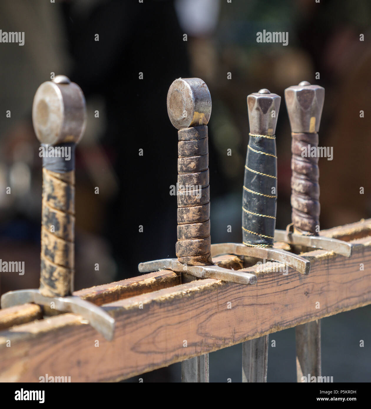 Handles of historical swords hung in a row on a medieval market, Germany - Stock Image