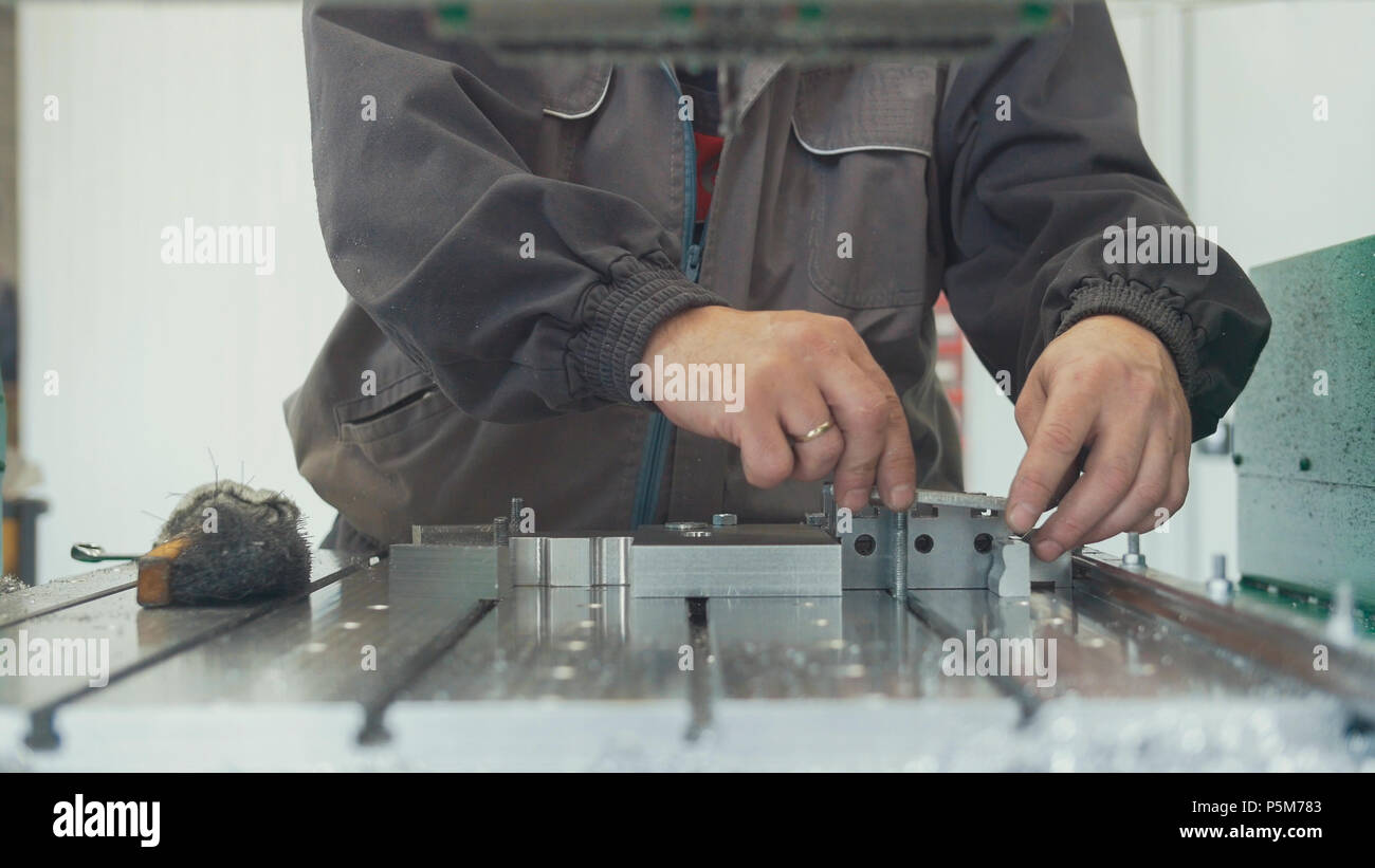 Worker with a scraper chamfering removing burrs on metal object for manufacturing industrial CNC machines - Stock Image