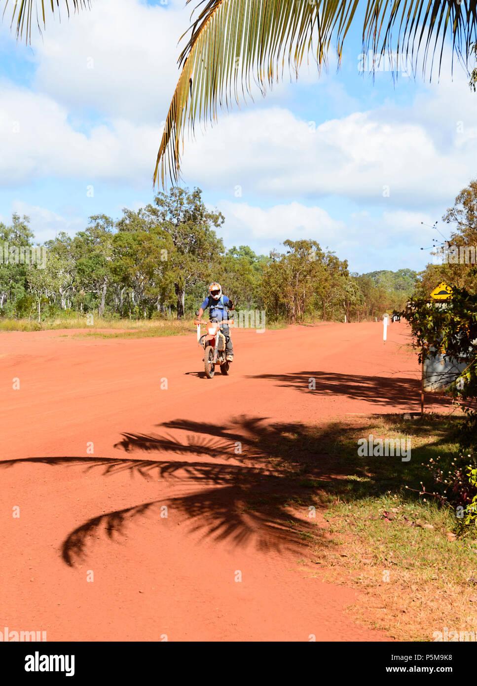 Motorbiker riding a dirt bike on a remote red dirt road, Cape York Peninsula, Far North Queensland, FNQ, QLD, Australia - Stock Image