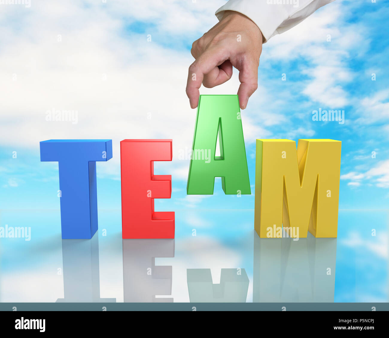 Assembling TEAM 3D word on table with blue sky reflection Stock Photo