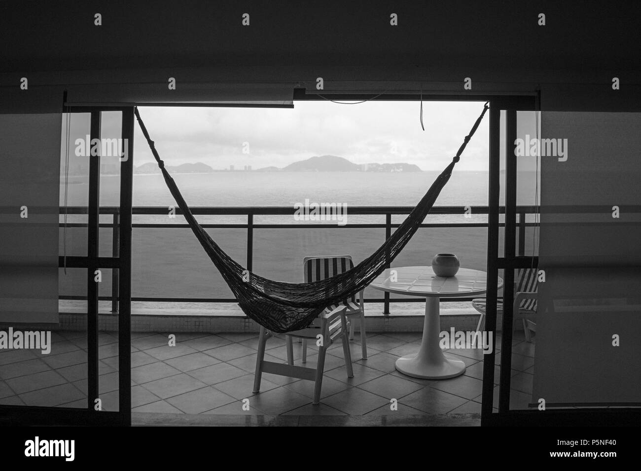 balcony ocean view blue hammock nobody black white - Stock Image