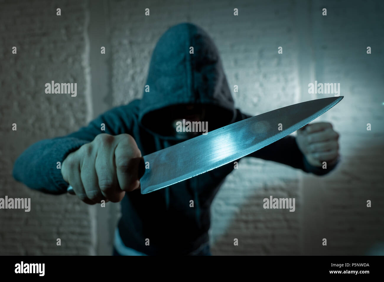 close up of a hands holding a knife of dangerous hooded man standing in the dark in London knife crime concept. - Stock Image