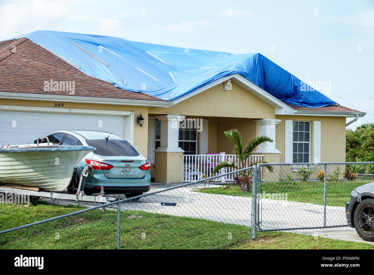 Fort Ft. Myers Florida Lehigh Acres after Hurricane Irma storm wind damage destruction aftermath blue tarp waterproof covering roof house home residen - Stock Image