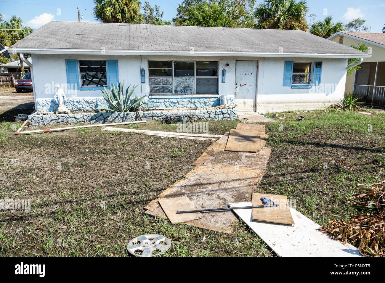 Bonita Springs Florida after Hurricane Irma damage destruction aftermath flooding house home muddy yard plywood pathway exterior flood depth water lin - Stock Image