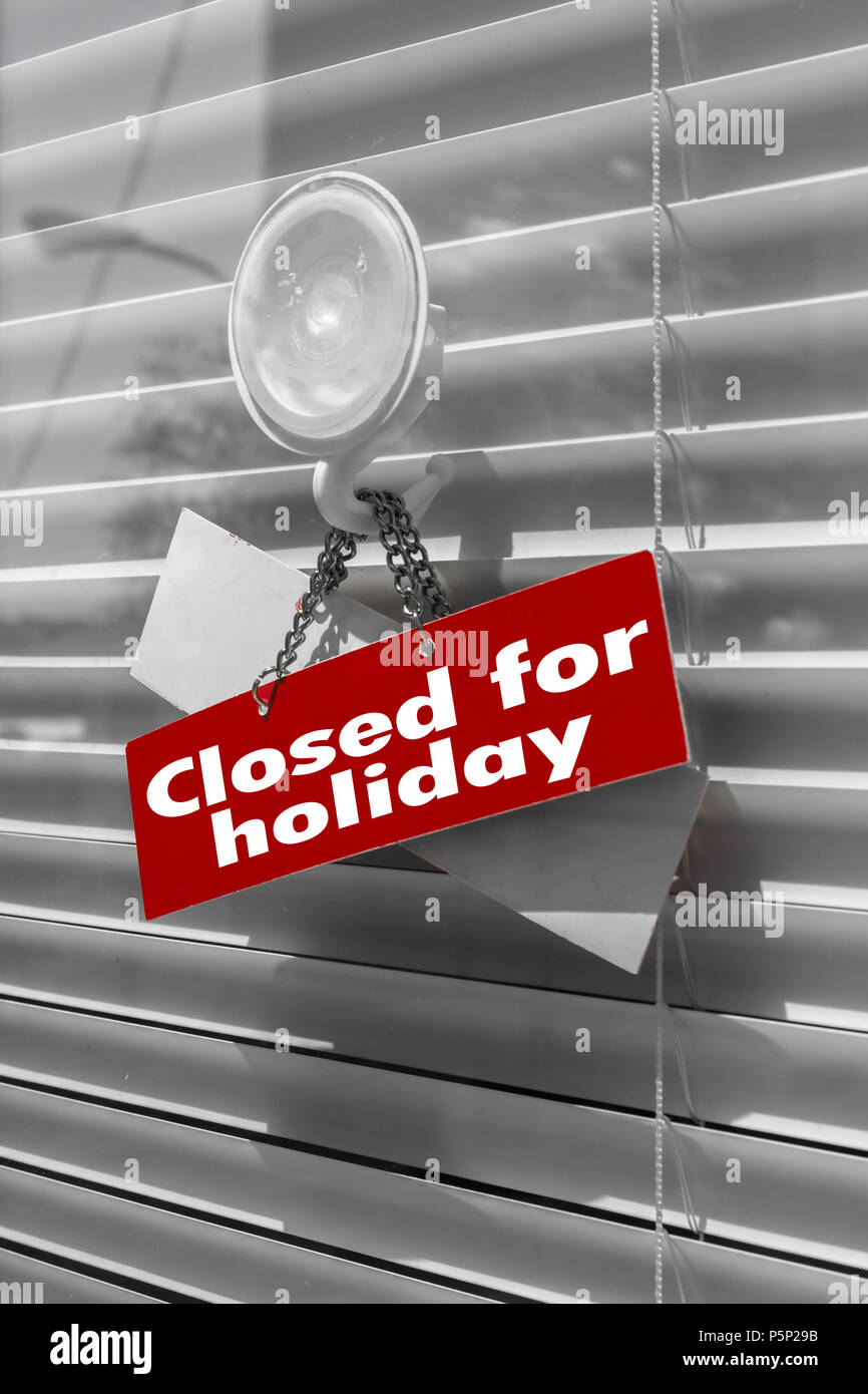 Sign Saying Closed For Holiday On A Glass Door With A White