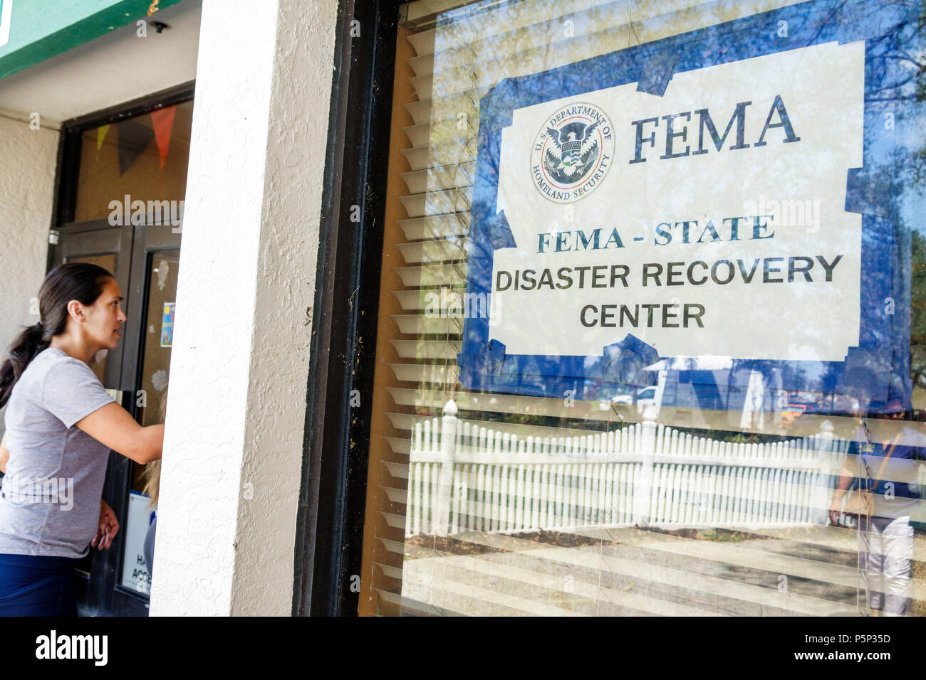 Immokalee Florida FEMA State Disaster Recovery Center centre storm assistance relief sign door Hispanic woman entering - Stock Image