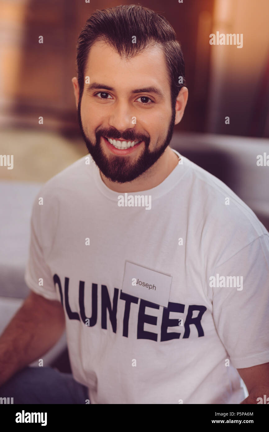Positive delighted volunteer posing at camera - Stock Image