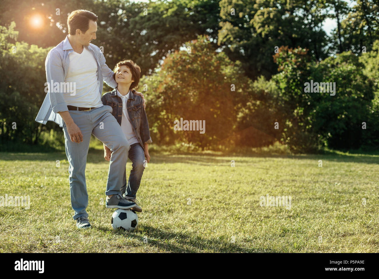 Dad and boy having a rest while playing football - Stock Image