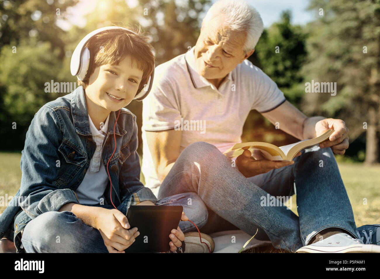 Smiling boy with his tablet and headphones sitting with grandpa - Stock Image