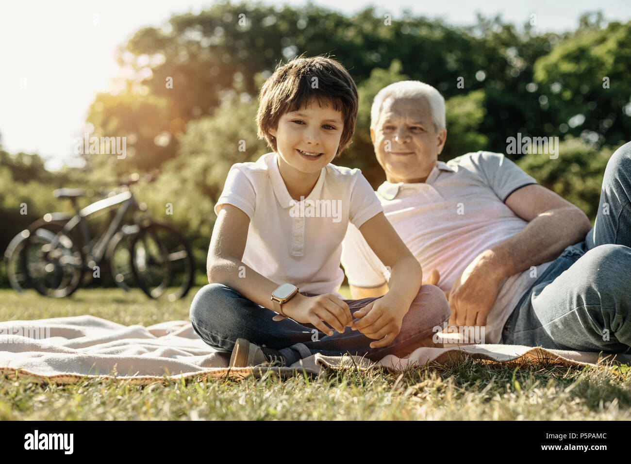 Smiling boy relaxing with his grandpa - Stock Image