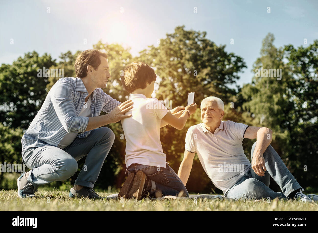 Boy and dad taking picture of grandpa - Stock Image