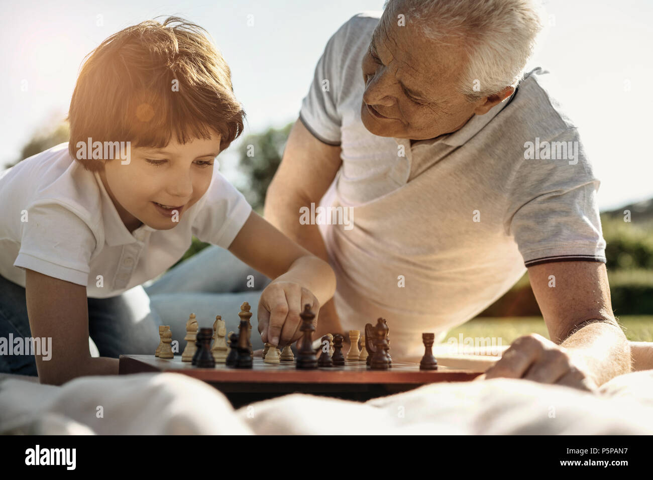 Boy and his grandpa playing chess - Stock Image