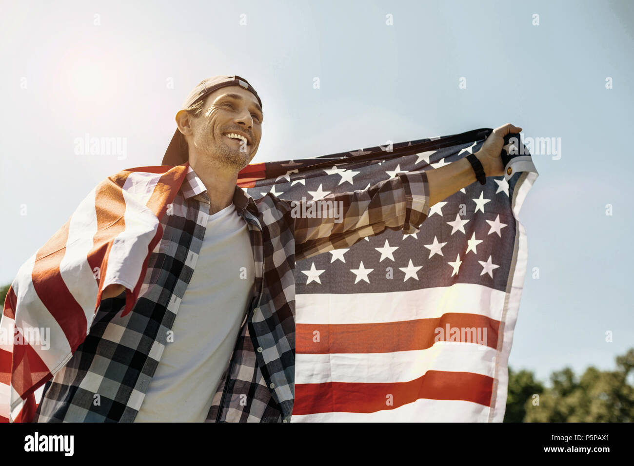 Cheerful man holding a flag and smiling - Stock Image