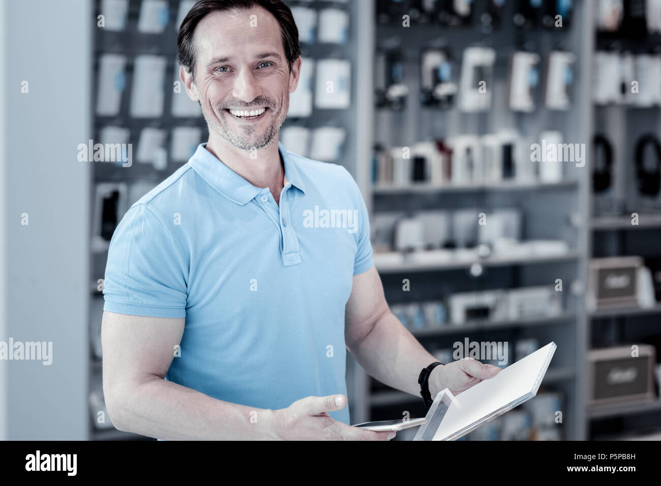 Positive man standing in the electronics shop - Stock Image