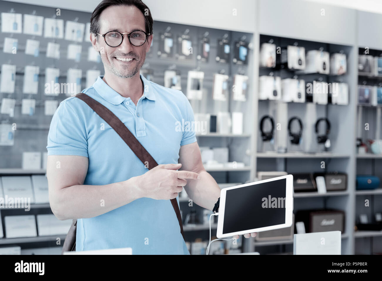Kind man pointing at the big tablet - Stock Image