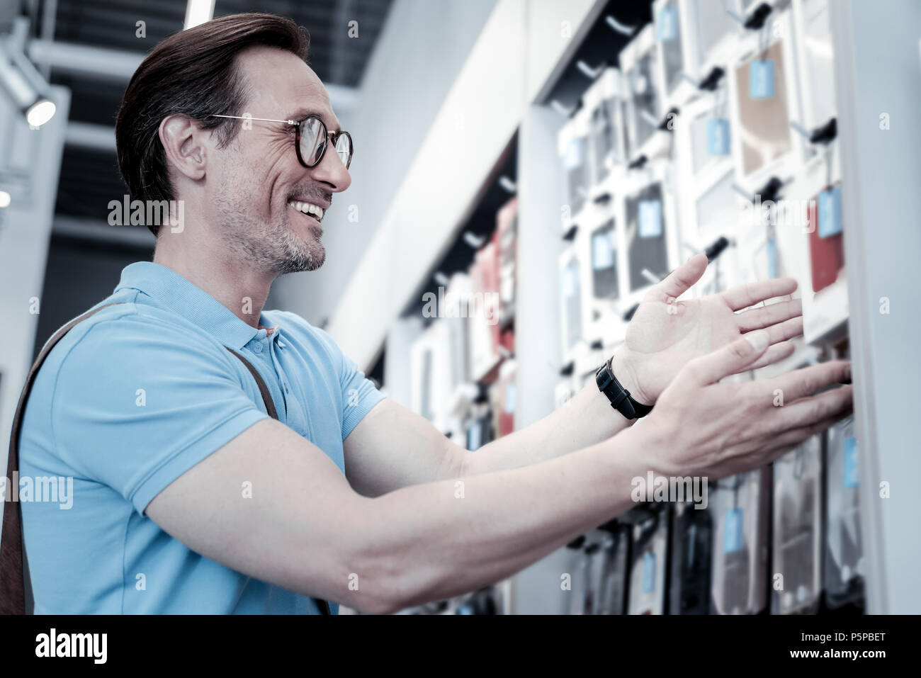 Cheerful man admiring smartphone cases - Stock Image