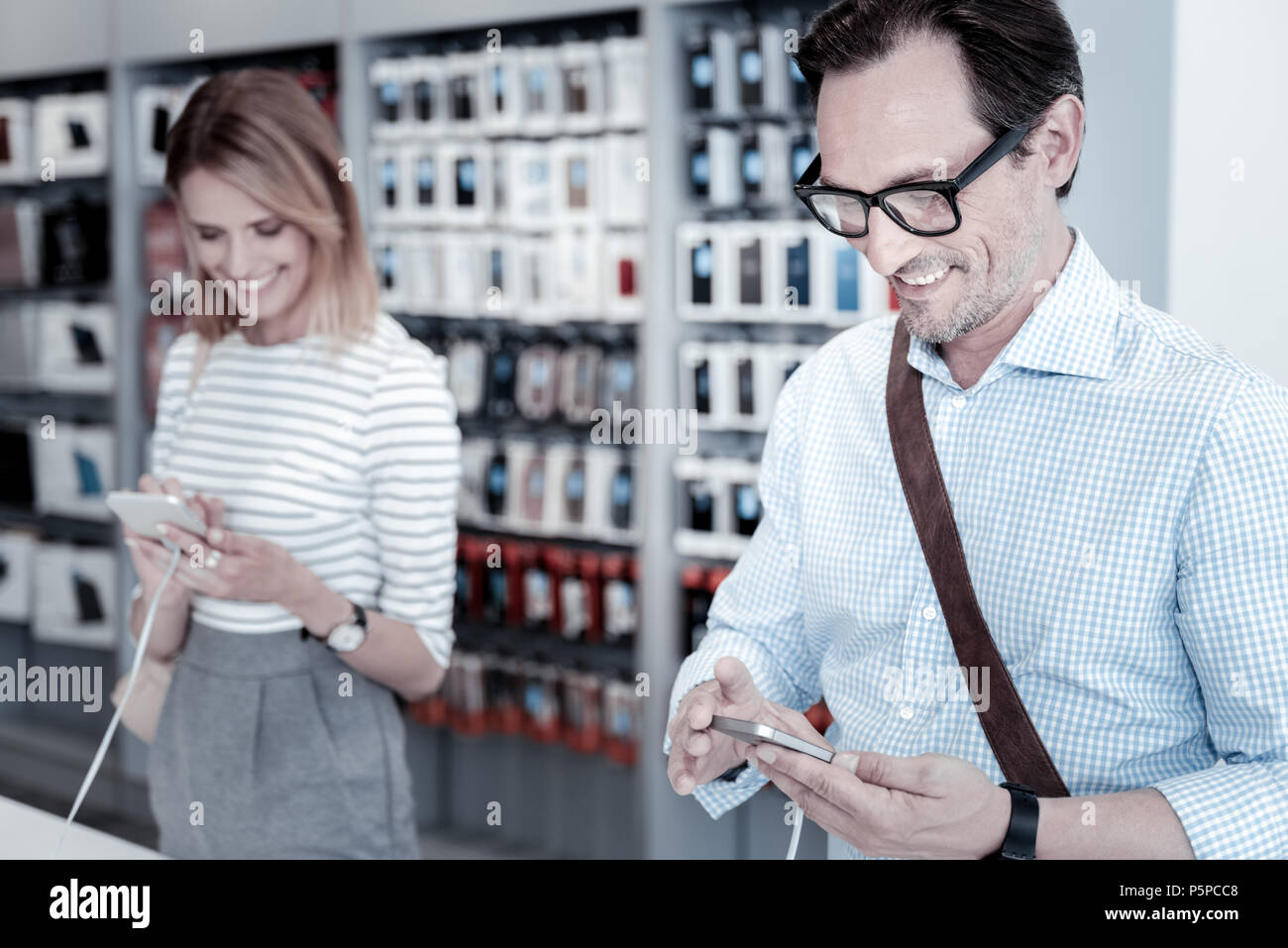Calm customers testing devices in a shop - Stock Image