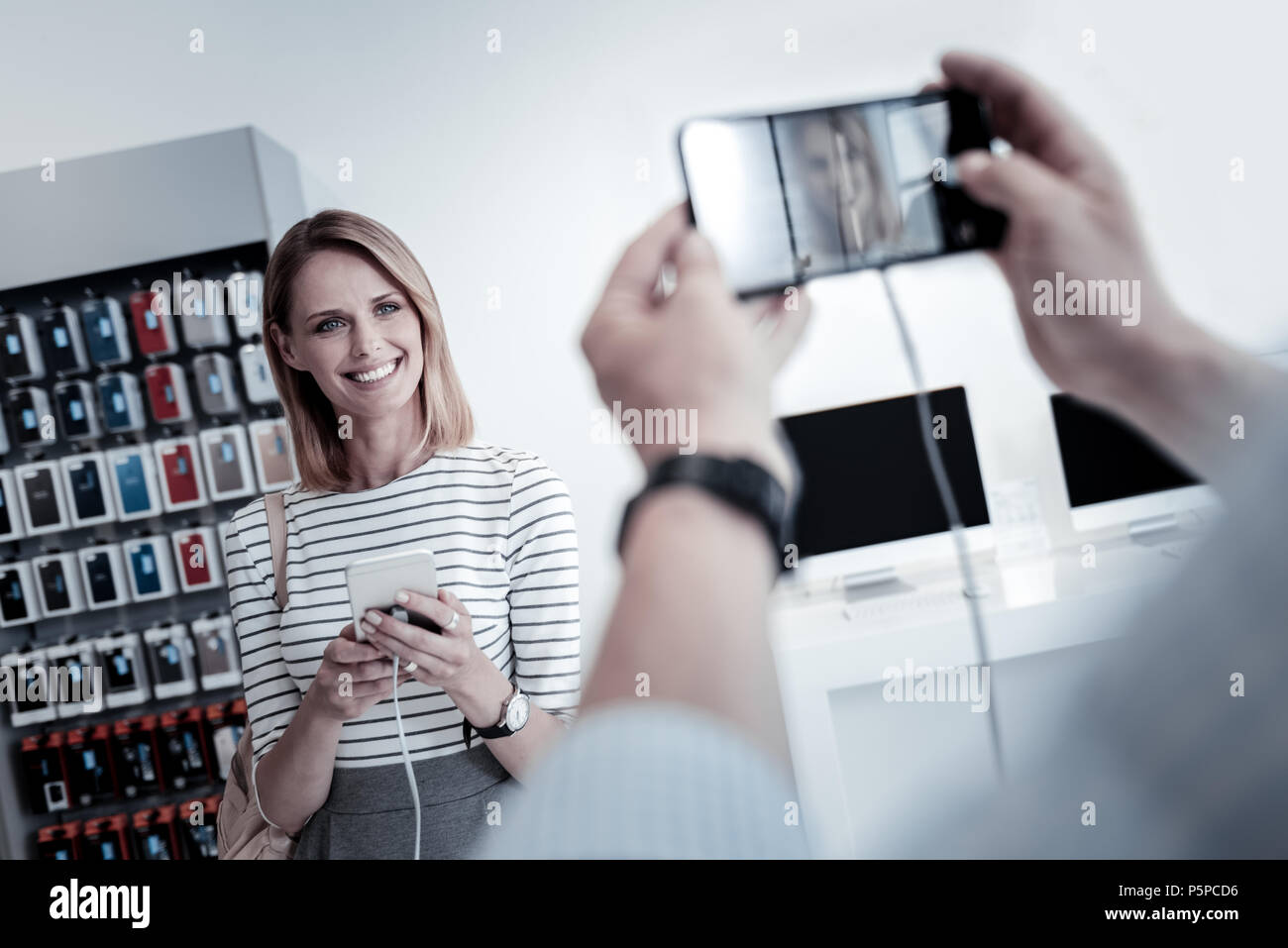 Pretty young woman looking happy at the photo - Stock Image