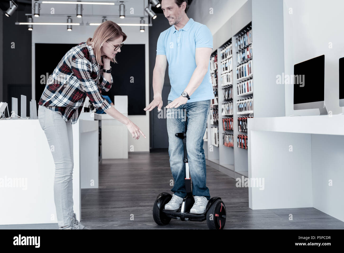 Shop assistant demonstrating a self balancing scooter - Stock Image