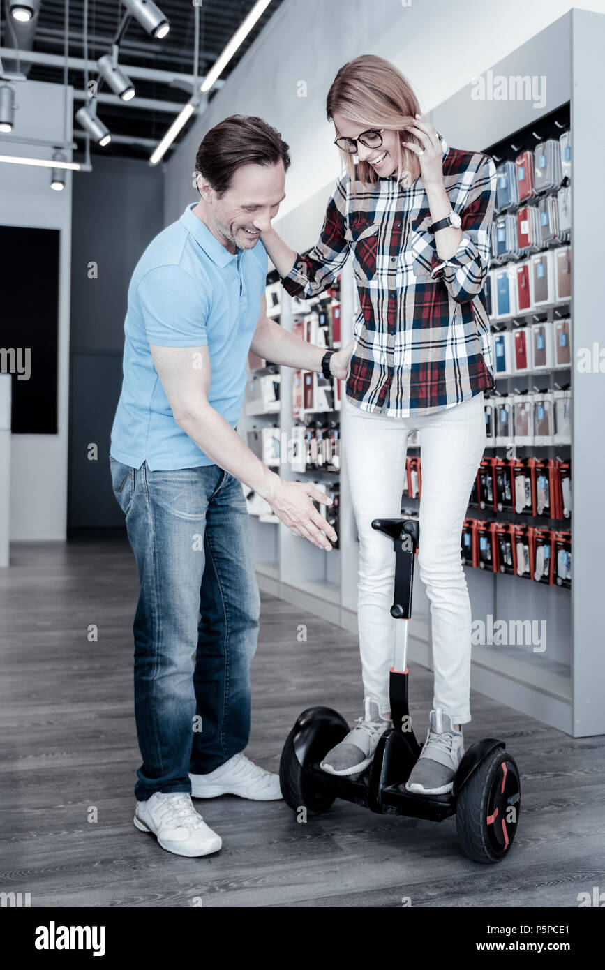 Lovely woman standing on a self balancing scooter - Stock Image