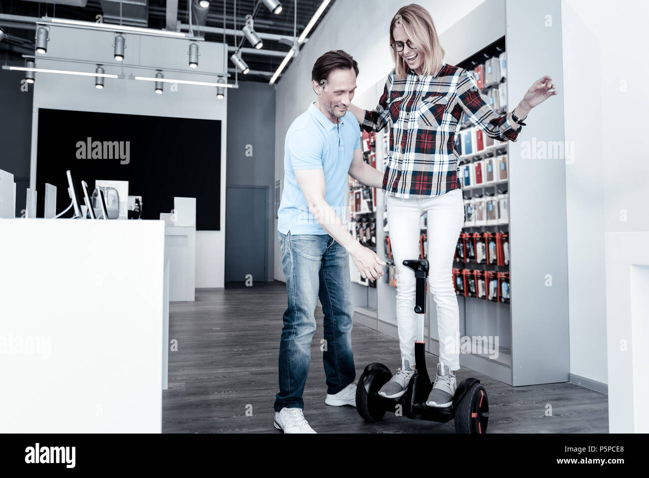 Emotional woman testing a self balancing scooter - Stock Image
