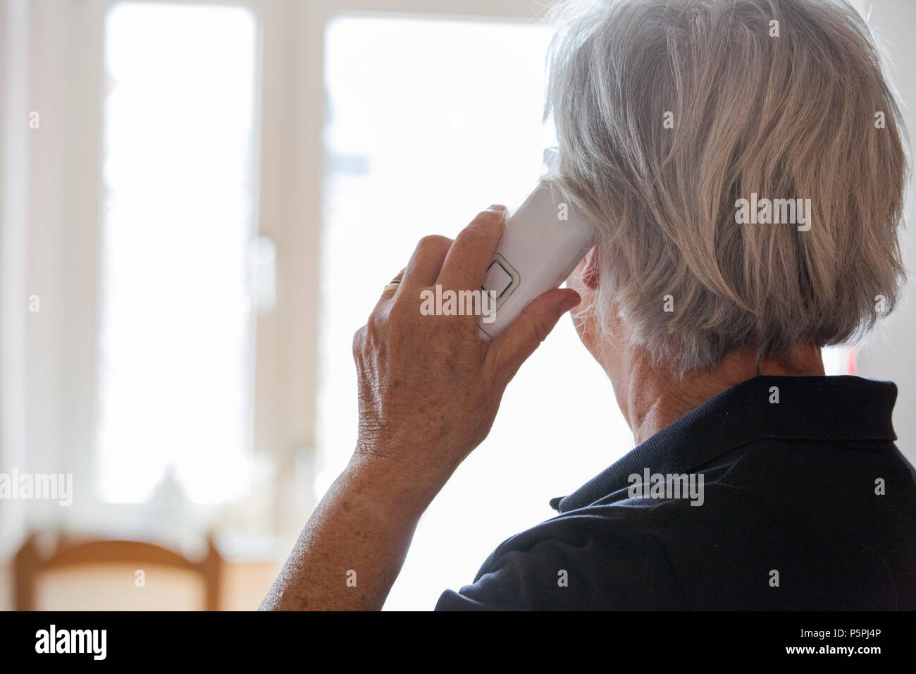 ältere Person am Telefon Hilfe suchend, elderly person on the phone looking for help - Stock Image