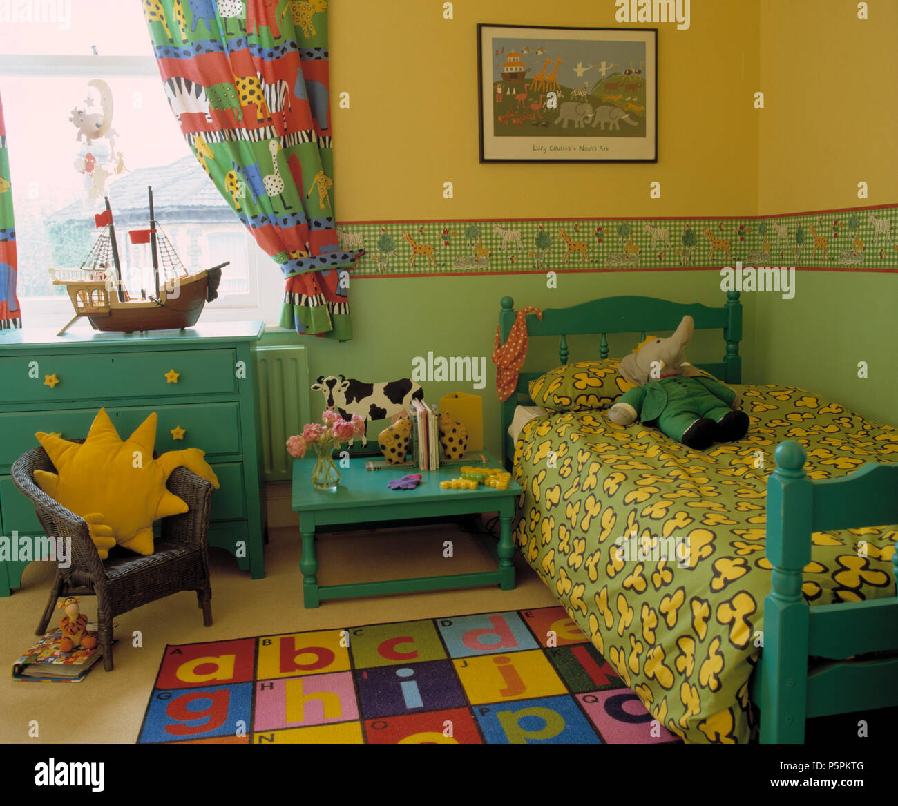 Turquoise Painted Furniture In Children S Colourful Nineties Bedroom With Dado Wallpaper Border Stock Photo Alamy
