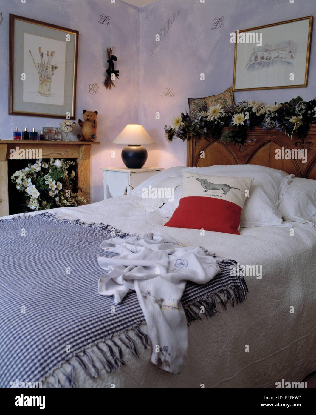 Blue+white checked throw and white bed linen on carved ooden ...