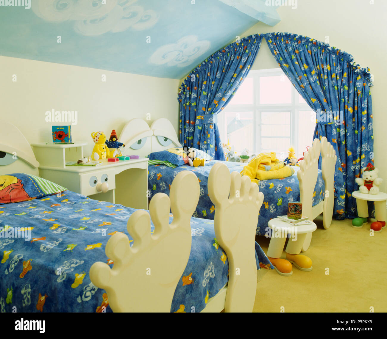Patterned Blue Curtains At Window In Children S Attic Bedroom With Foot Shaped Footboards On Twin Beds Stock Photo Alamy