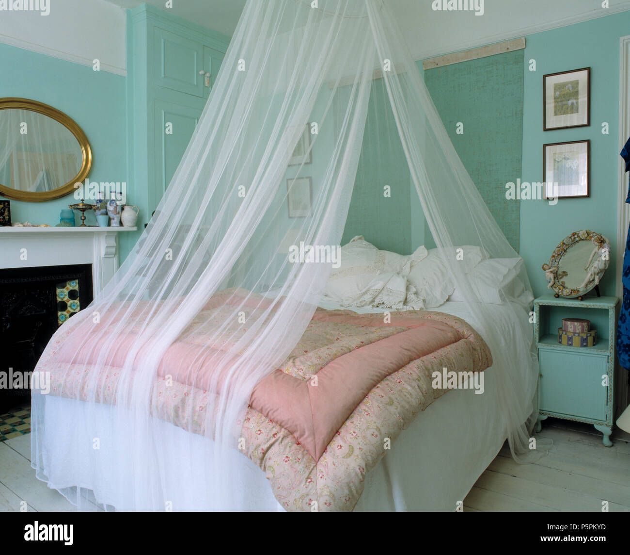 White voile drapes above bed with pink vintage eiderdown and ...