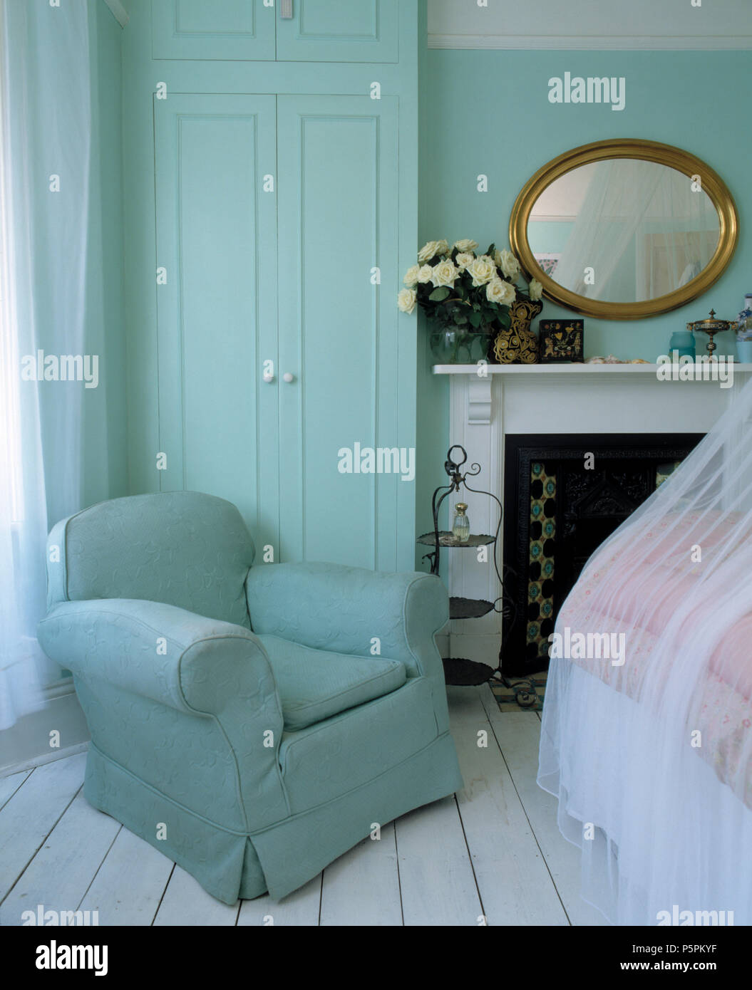 Pale turquoise armchair and white painted floorboards in ...
