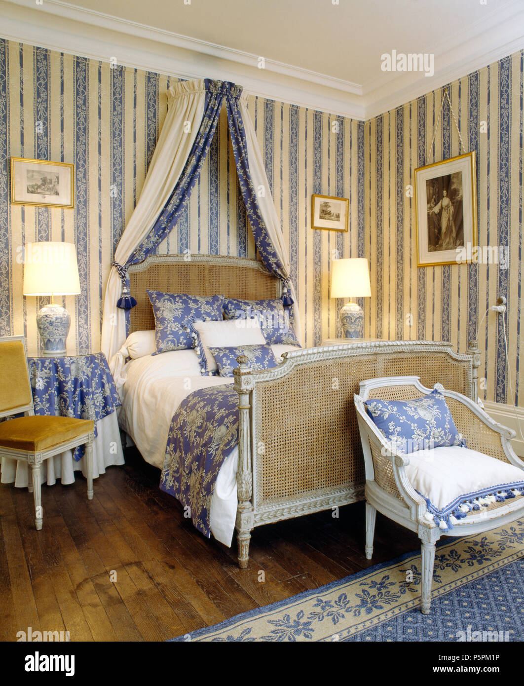 Antique Bergere bed with blue drapes in French country ...