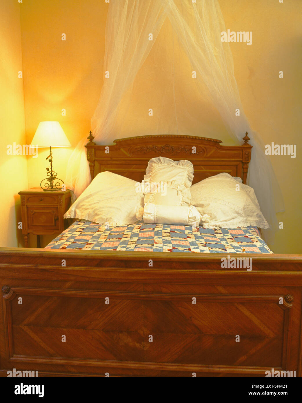 Lighted Lamp On Table Beside Vintage Wooden Bed With White Cushions And White Voile Drapes In Yellow Country Bedroom Stock Photo Alamy