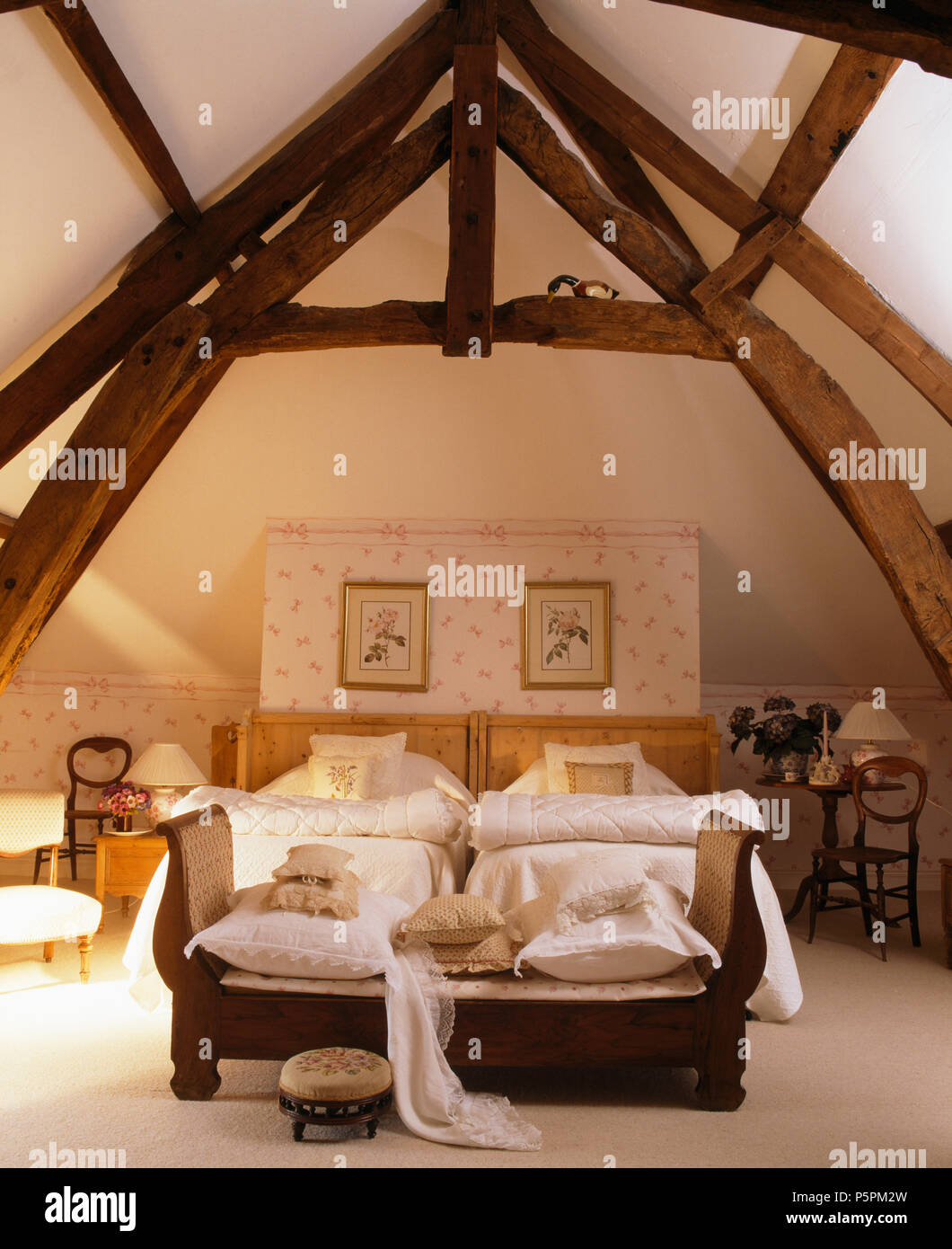High, beamed apex ceiling in French country bedroom with sofa at the foot of twin beds with white quilts Stock Photo