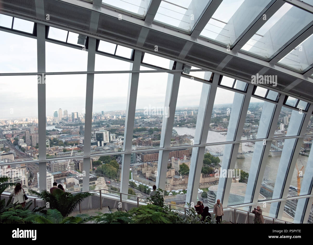 Large windows with view of London from the Sky Garden, 20 Fenchurch St. Known as the Walkie Talkie. People on stairs, plants in foreground. Horizontal - Stock Image