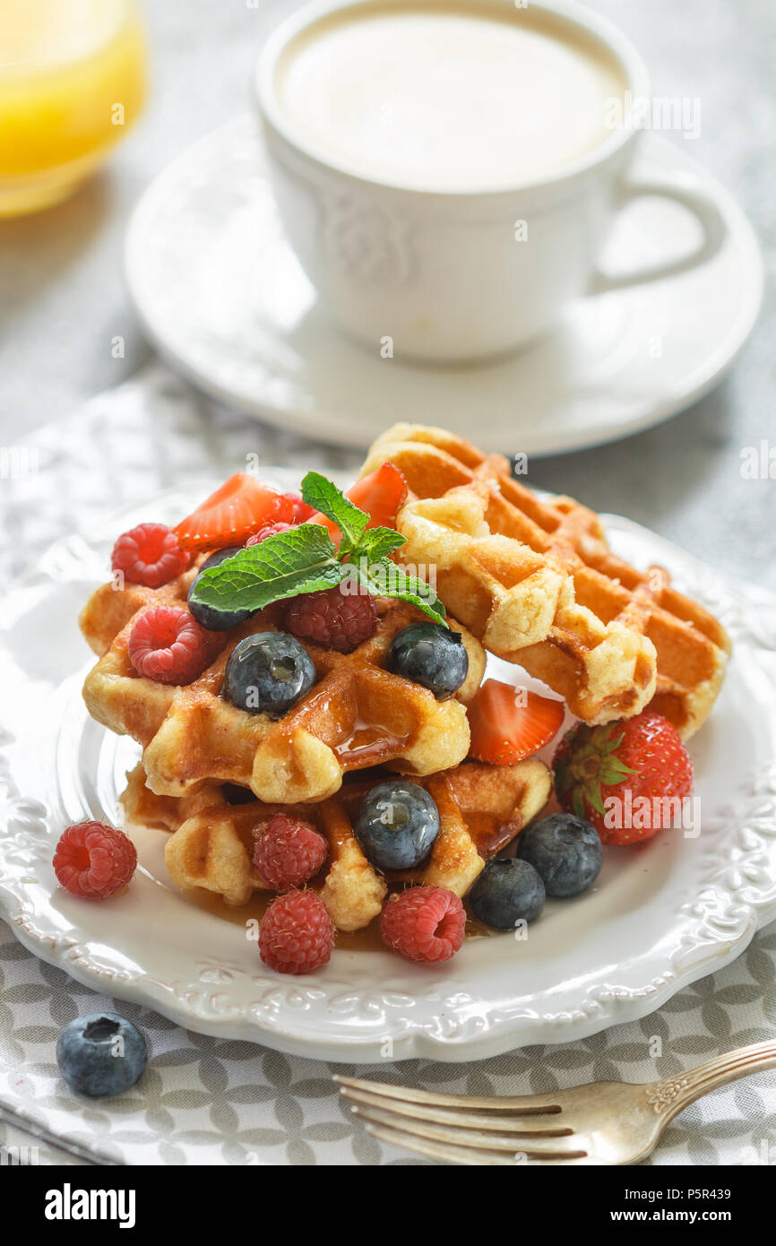 Fresh homemade waffles with raspberries, strawberries, blueberries and honey. Delicious Breakfast with berries, cappuccino and orange juice . Selectiv - Stock Image