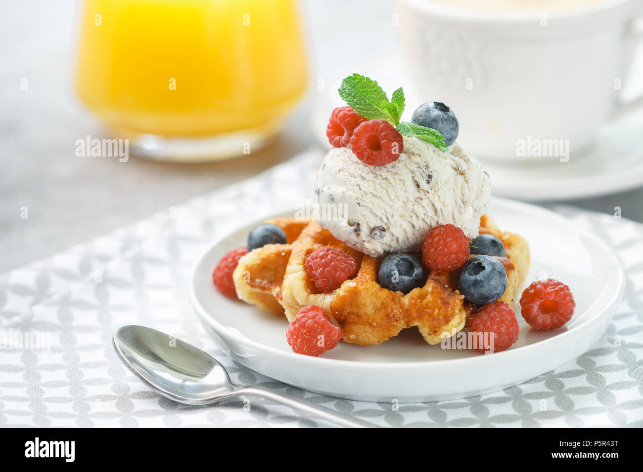 Homemade waffles with ice cream and fresh berries-raspberries, blueberries. Delicious dessert, cappuccino and orange juice on the table. Selective foc - Stock Image