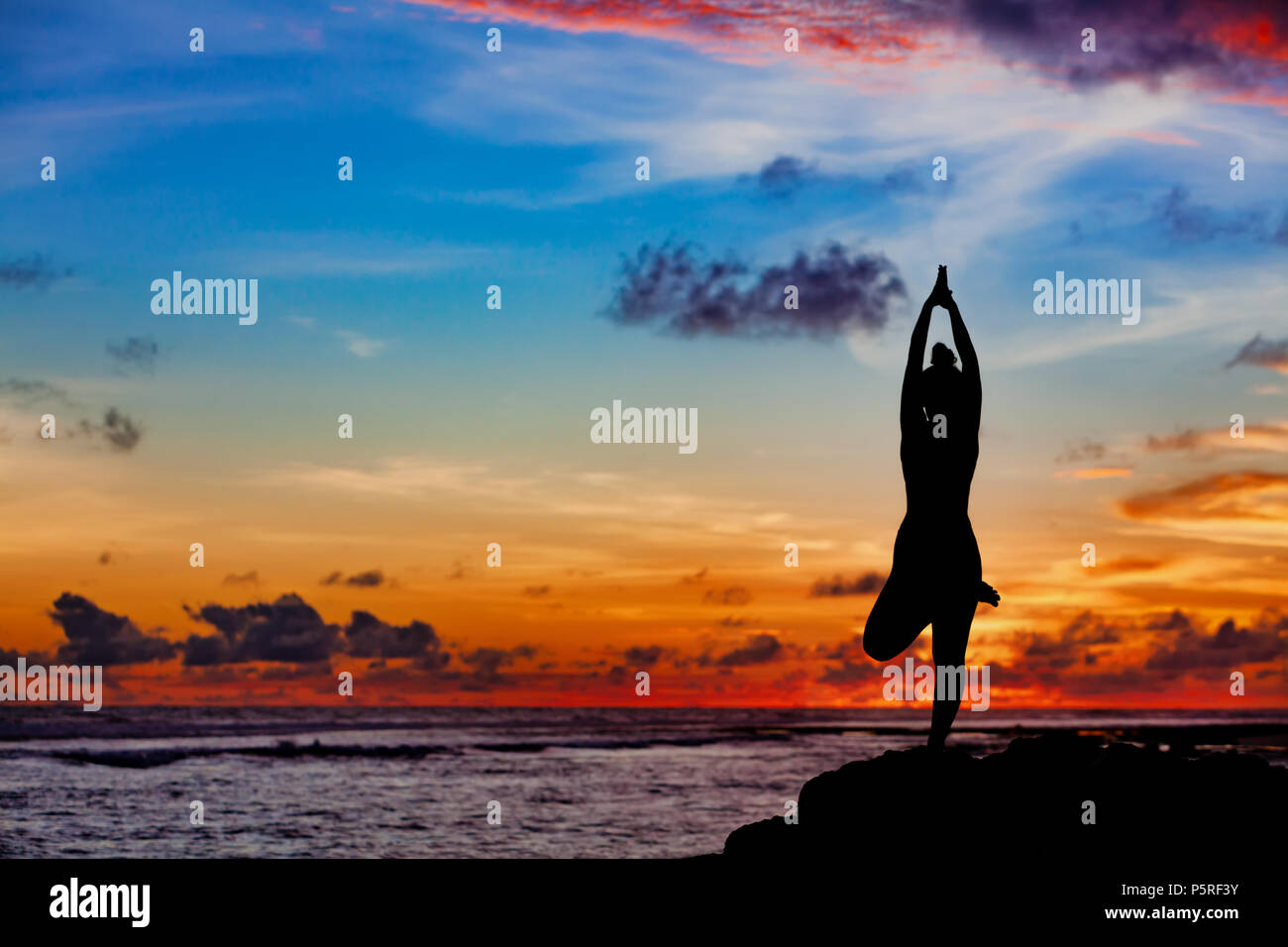 Sunset meditation silhouette Active woman stand in yoga pose on beach rock to keep fit and health. Healthy lifestyle, fitness training, sport activity - Stock Image