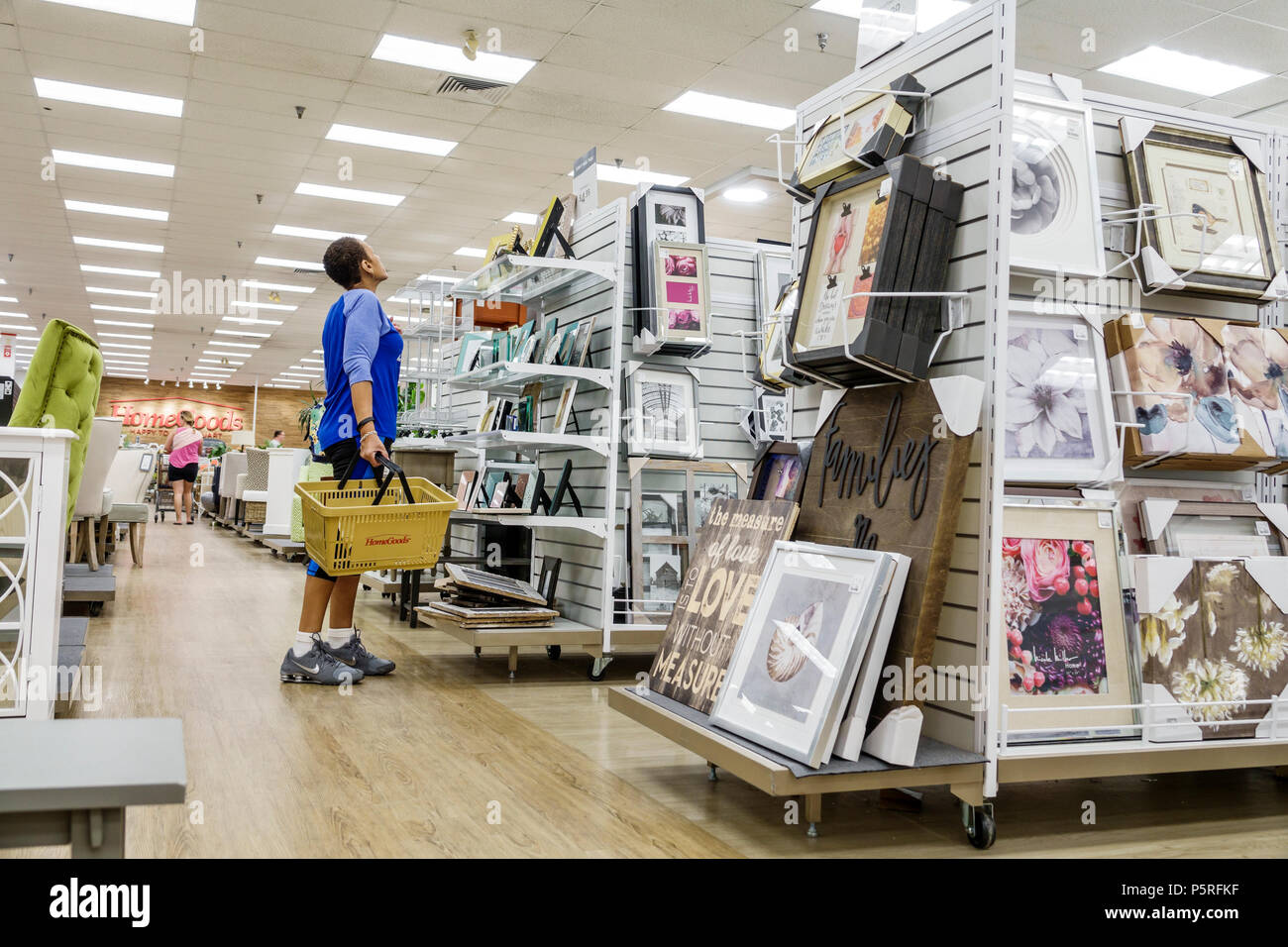 Stuart Florida HomeGoods Discount Home Furnishings Decor Display Sale Shopping Interior Frames Pictures Black Woman Looking Shelves