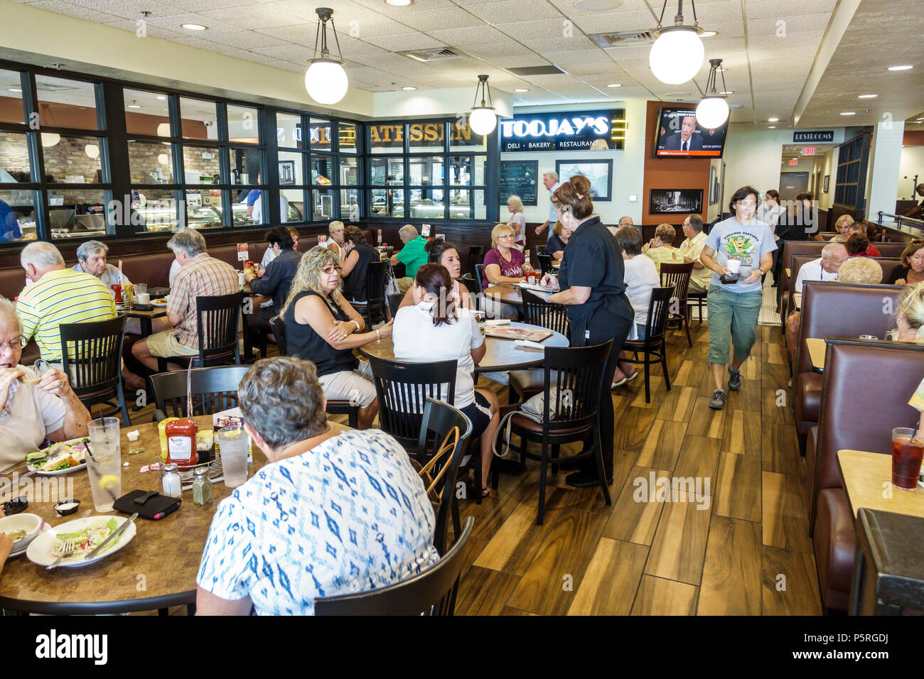 Crowded Restaurant Table In Stuart Florida Toojays Gourmet Deli Restaurant Interior Tables Patrons Customers Crowded Busy Man Woman Waitress Seniors Mature Adults