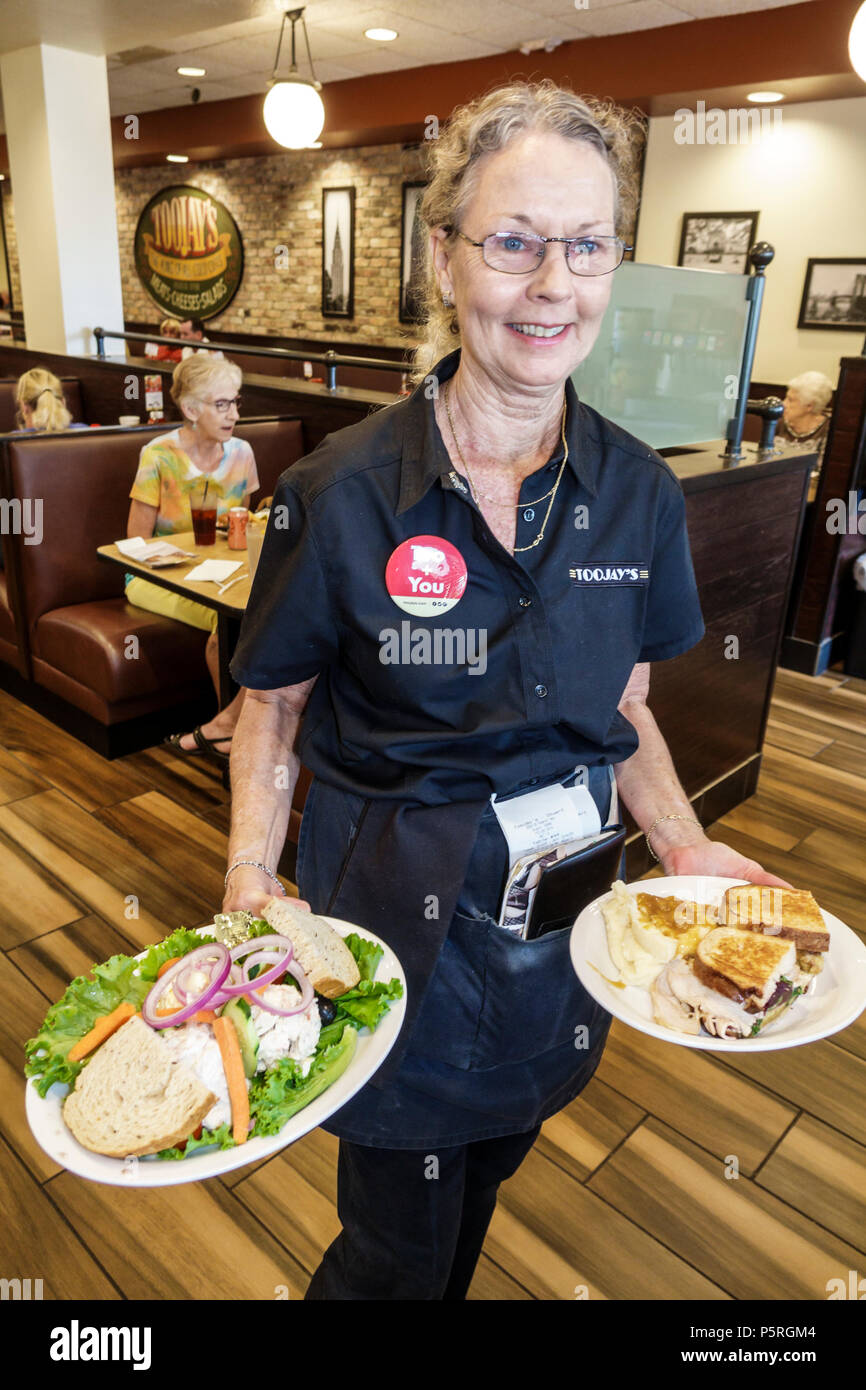 Stuart Florida TooJay's Gourmet Deli restaurant interior mature woman waitress server serving carrying food plates sandwich - Stock Image