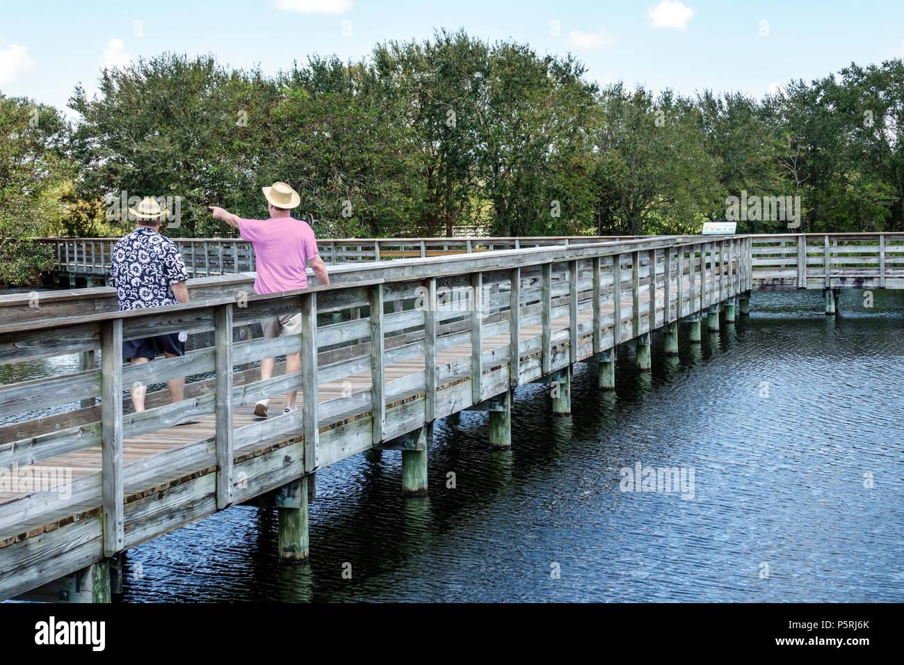 Delray Beach Florida Wakodahatchee Wetlands nature wildlife preserve park boardwalk trail protected bird habitat water reclamation project man hiker w - Stock Image