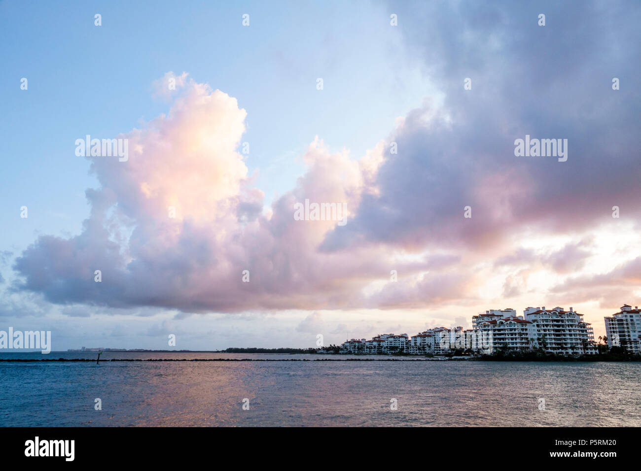 Miami Beach Florida Fisher Island Government Cut Atlantic Ocean water city skyline cumulonimbus cloud backlit sunset sky - Stock Image