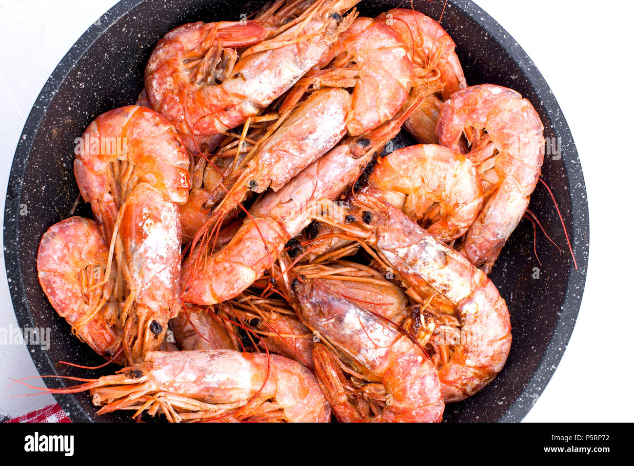 Large shrimps fried in a frying pan. On a white table. Lunch from seafood. Free space for text. Copy space - Stock Image