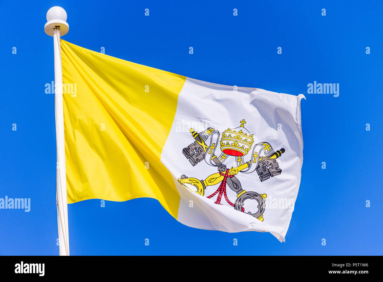 The flag of the Vatican City against a blue sky. - Stock Image