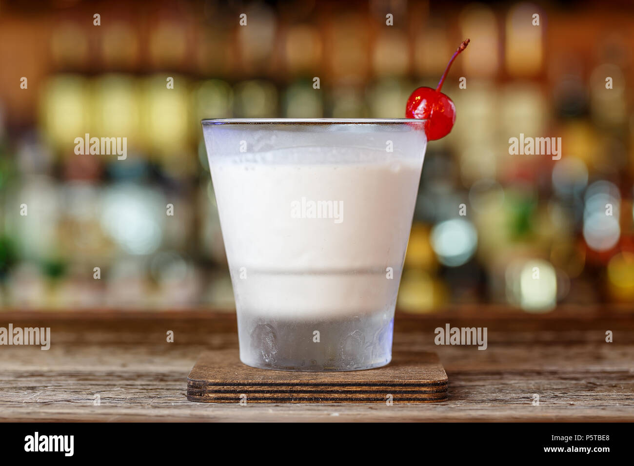 White Russian cocktail stands on the bar in the restaurant on a blurry bottle background Stock Photo