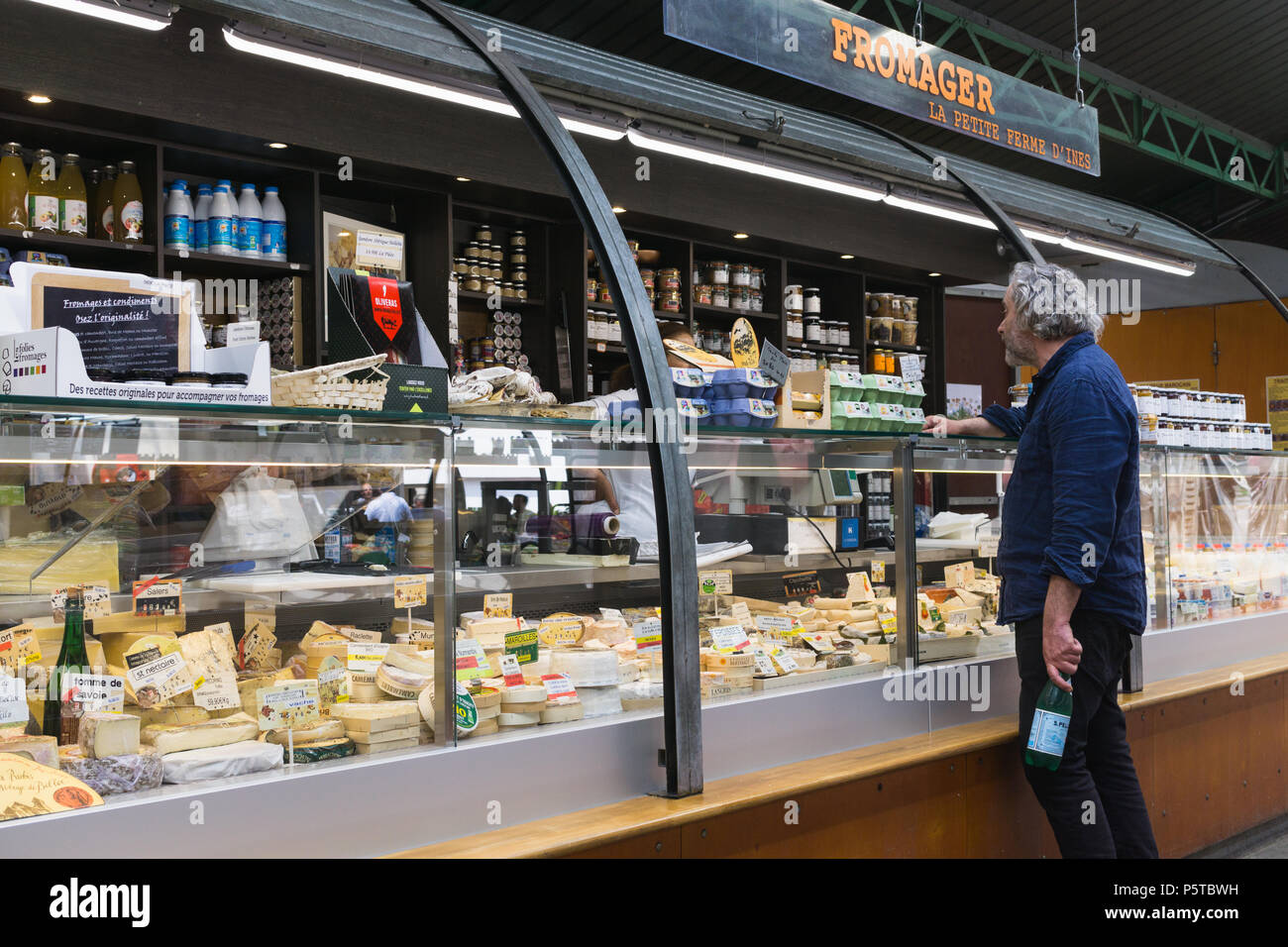 Cheese for sale in a Paris cheese shop (fromagerie) at the Enfants Rouges market, France. - Stock Image