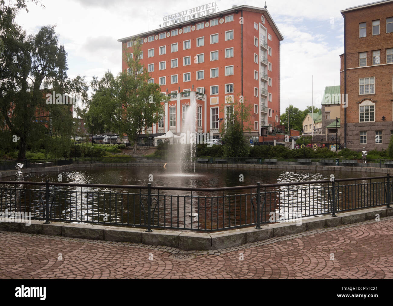 City park with fountain in front of the Radisson Blu Grand Hotel Tammer, in Tampere Finland - Stock Image