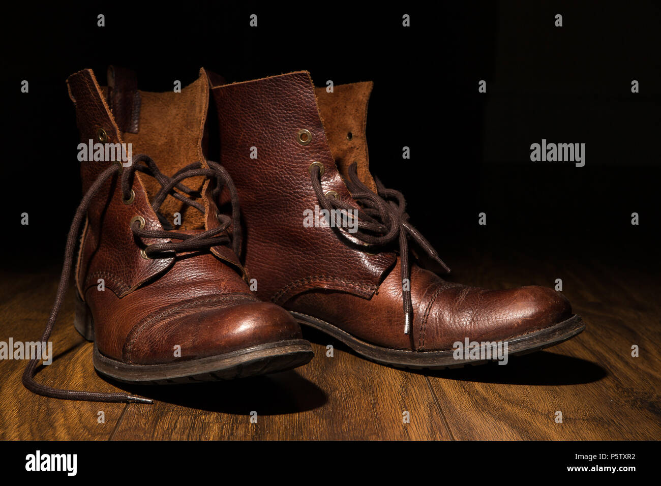 Arty close up of men's brown, leather ankle boots, laces undone, on wooden flooring with dark background. Low-key lighting used for artistic effect. - Stock Image